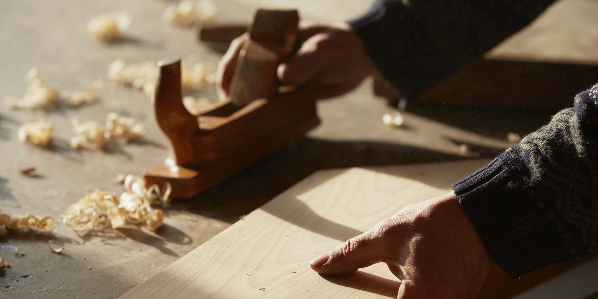 Wood plane with wood shavings and worker's hands